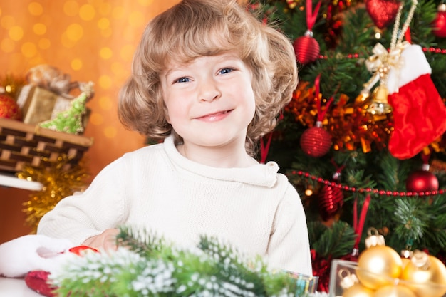 Glückliches lächelndes kind gegen geschmückten weihnachtsbaum