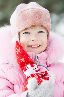 Glückliches lächelndes kind mit weihnachtsdekoration im winterpark