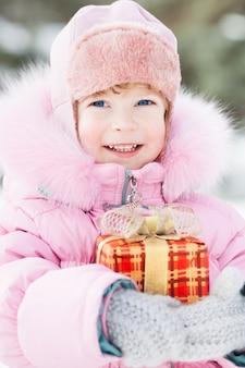 Glückliches lächelndes kind mit weihnachtsgeschenk im winterpark