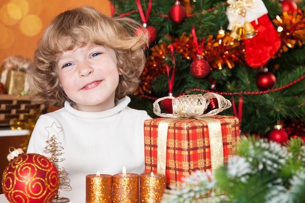 Glückliches lächelndes kind mit weihnachtsschmuck