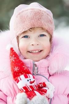 Glückliches lächelndes kind mit weihnachtsschneemann im winterpark