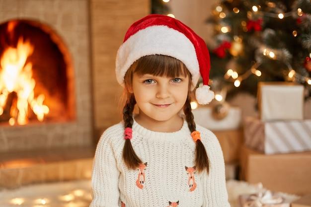 Glückliches lächelndes kindermädchen, das zu hause im dekorierten wohnzimmer aufwirft