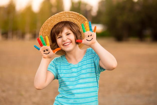 Glückliches lächelndes kleines mädchen mit den händen in der farbe spielen im freien im sommerpark