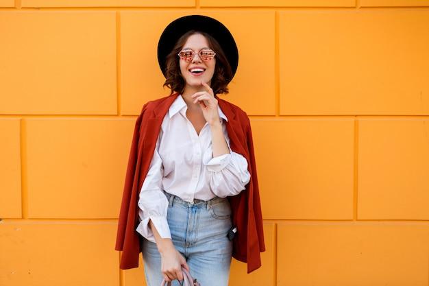Glückliches lächelndes kurzhaariges mädchen, das über gelber wand aufwirft. warme farben. positive stimmung.