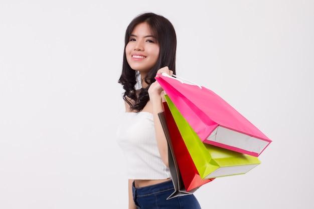 Glückliches lächelndes mädchen beim einkaufen, aufgeregte frau, die einkaufstasche isoliert hält, lächelndes mädchen, glückliche frau, die bunte tasche einkauft, asiatische dame glückliches einkaufskonzept süßes hübsches mädchen schöne frau asiatisches modell