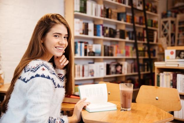 Glückliches lächelndes mädchen, das am tisch sitzt und ein buch in der bibliothek liest