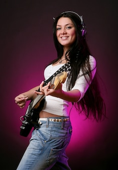 Glückliches lächelndes mädchen, das gitarre spielt