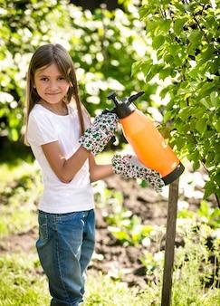 Glückliches lächelndes mädchen, das kleinen apfelbaum mit düngemitteln sprüht