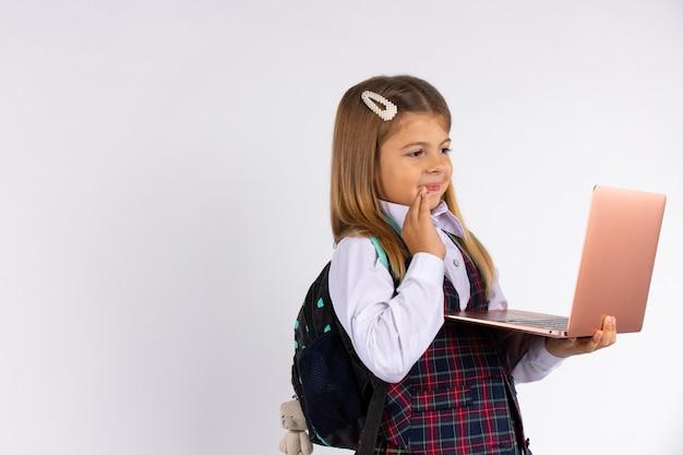 Glückliches lächelndes mädchen, das schuluniform trägt, einen rucksack und einen laptop-computer hält, zeigt hallo, lokalisiert auf grauer wand. online-fernlehrkonzept, porträt.