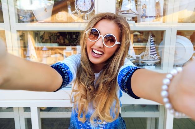 Glückliches lächelndes mädchen, das selfie, lustiges verspieltes bild der lachenden frau nimmt, die nahe souvenirfenstereinkauf hellen hellen stilvollen pullover und sonnenbrille aufwirft.