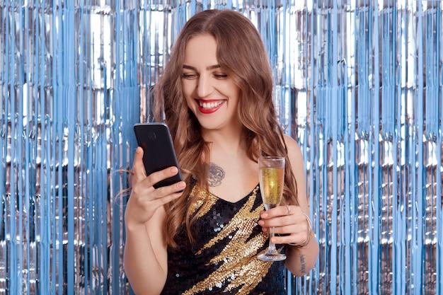 Glückliches lächelndes mädchen, das smartphone und glas wein in den händen verwendet, modell, das stilvolles elegantes schwarzes kleid trägt, auf den bildschirm des geräts schaut und glücklich mit glitzer-lametta auf raum lacht.