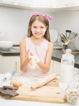 Glückliches lächelndes mädchen, das teig für kuchen auf küche macht
