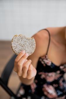 Glückliches lächelndes mädchen hält keks in einem gemütlichen café. ansicht schließen