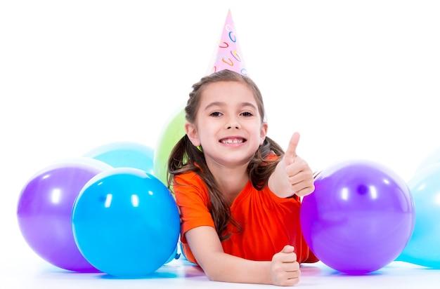 Glückliches lächelndes mädchen im orangefarbenen t-shirt, das auf dem boden mit bunten luftballons liegt und daumen hoch zeigt - lokalisiert auf einem weiß