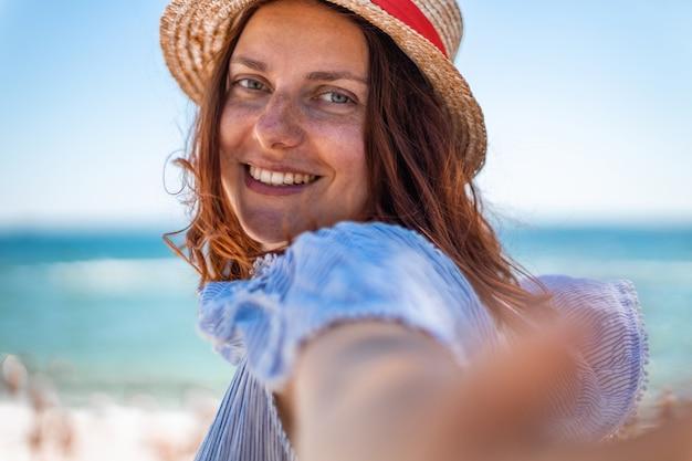 Glückliches lächelndes mädchen im strohhut, das kamera am strand betrachtet