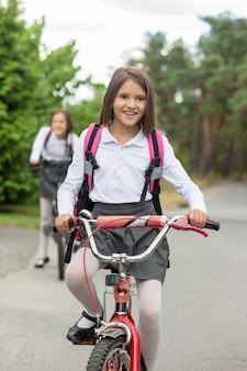 Glückliches lächelndes mädchen in der schuluniform, die fahrrad fährt