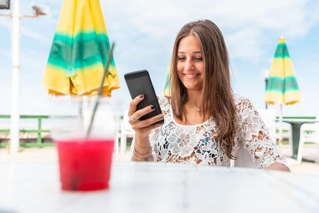 Glückliches lächelndes mädchen mit telefon und matsch am meer