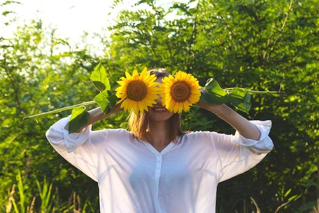 Glückliches lächelndes mädchen schließt ihre augen mit gelben sonnenblumen