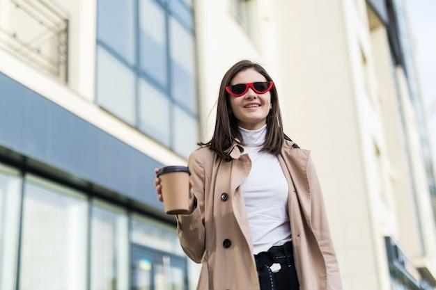 Glückliches lächelndes modell im hellbraunen mantel trinkt kaffee draußen