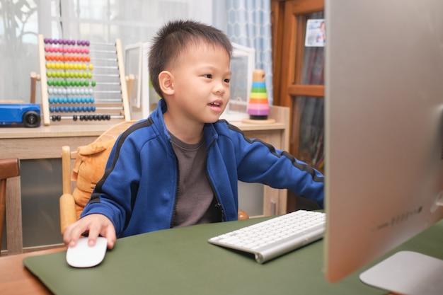 Glückliches lächelndes niedliches kleines asiatisches kind mit personalcomputer, der zu hause videoanruf macht, kindergartenjunge, der online studiert und schule über e-learning besucht