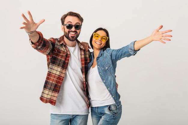 Glückliches lächelndes paar, das hände in der kamera lokalisiert auf weißem studio hält