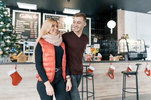 Glückliches lächelndes paar, das im kaffeehaus in der wintersaison umarmt