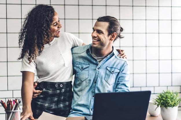 Glückliches lächelndes paar, das mit laptop-computer zusammen arbeitet. kreative geschäftspaarplanung und brainstorming im wohnzimmer zu hause
