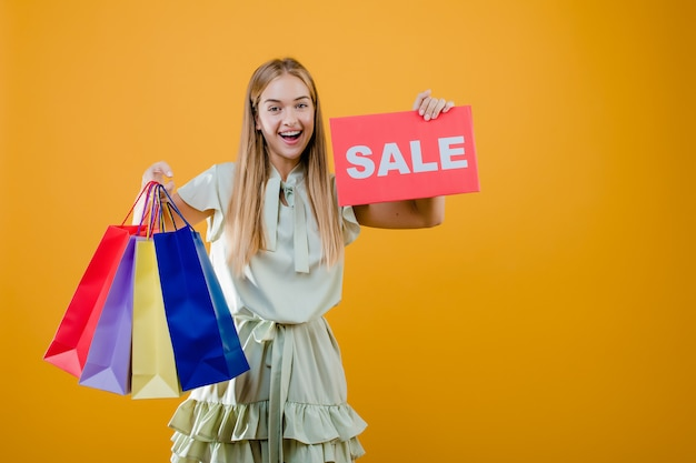 Glückliches lächelndes recht blondes mädchen hat verkaufszeichen mit den bunten einkaufstaschen, die über gelb lokalisiert werden