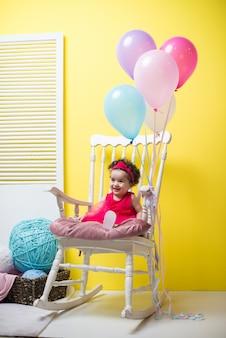Glückliches lächelndes süßes baby, das auf lehnsessel mit geburtstagsballonen sitzt