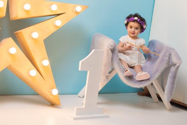 Glückliches lächelndes süßes baby, das auf lehnsessel mit glänzendem hellem stern sitzt