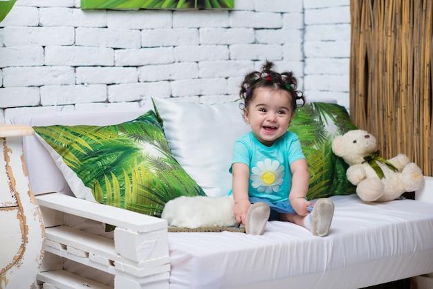 Glückliches lächelndes süßes baby, das auf sofa mit bärenspielzeug sitzt