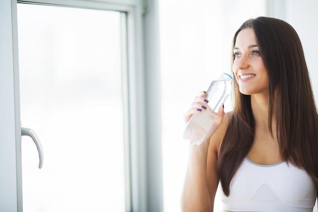 Glückliches lächelndes trinkwasser der jungen frau