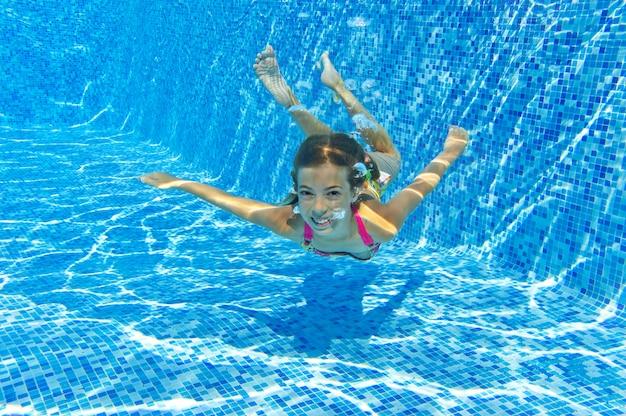 Glückliches lächelndes unterwasserkind im swimmingpool, schönes mädchen schwimmt und hat spaß. kindersport im familiensommerurlaub. aktivurlaub