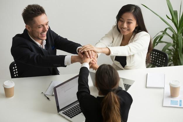 Glückliches lächelndes verschiedenes team schließen sich hände zusammen bei der gruppensitzung an