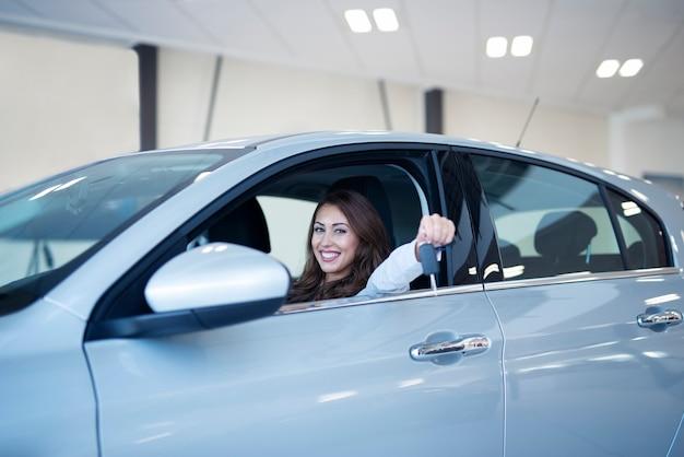 Glückliches lächelndes weibliches halten der schlüssel ihres brandneuen fahrzeugs