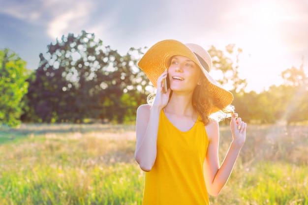 Glückliches lächelndes weibliches weibchen im sommerhut und im gelben sommerkleid des lite, das sprechend spricht durch smartphone, handy im grünen park im freien. sommer, frühling aktives outdoor-freizeitkonzept.