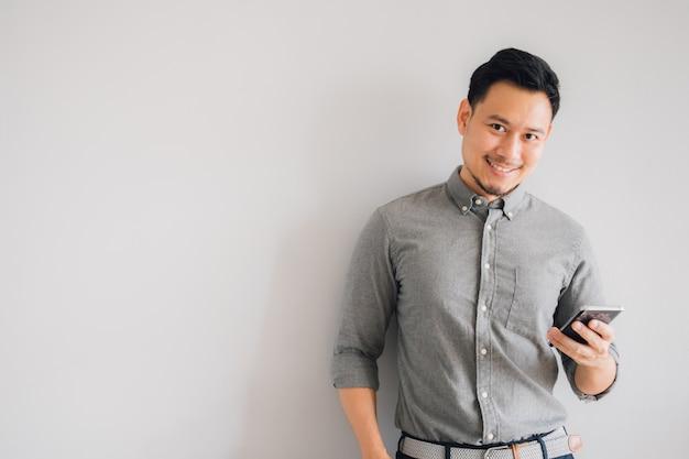 Glückliches lächelngesicht des hübschen asiatischen manngebrauchs-smartphonestands lokalisiert auf grauem hintergrund