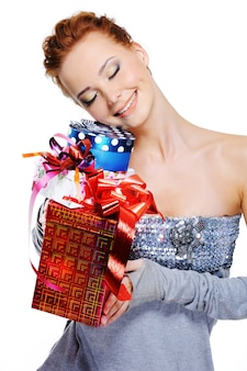 Glückliches lächelnmädchen, das weihnachtsgeschenke hält, schließen ihren kopf über leerraum