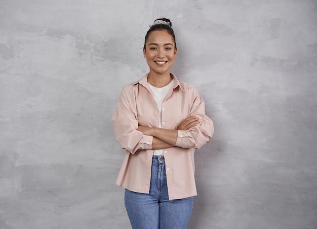 Glückliches lächelnporträt einer fröhlichen jungen frau in freizeitkleidung, die beim posieren in die kamera lächelt