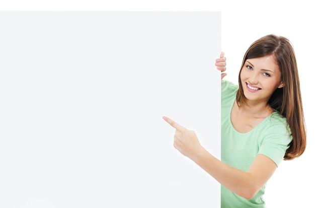 Glückliches lässiges erwachsenes mädchen, das auf der nachricht auf leerer plakatwand zeigt