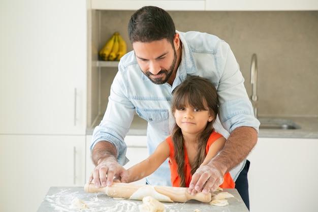 Glückliches lateinamerikanisches mädchen und ihr vater, die teig auf küchentisch mit mehlpulver rollen und kneten.