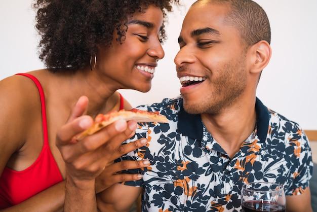 Glückliches lateinamerikanisches paar, das zusammen zu abend isst.