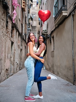 Glückliches lesbisches paar, das einen herzförmigen ballon umarmt und hält, während es zusammen auf der straße posiert. lgbt- und valentinstagskonzept.