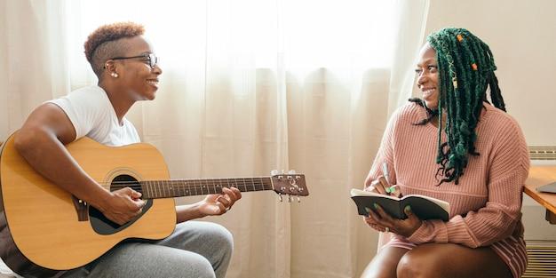 Glückliches lesbisches paar, das zusammen musik macht