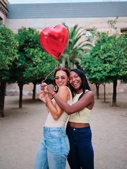 Glückliches lesbisches paar mit einem roten herzförmigen ballon beim stehen im freien auf der straße. lgbt- und valentinstagskonzept.