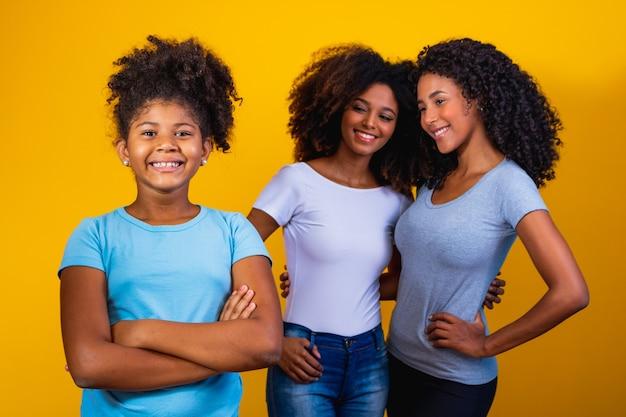 Glückliches lesbisches paar mit kind auf gelbem hintergrund. paar zusammen mit adoptivtochter, adoptionskonzept