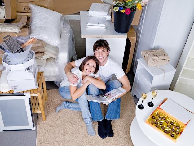 Glückliches liebendes lächelndes paar, das auf dem boden mit fotoalbum sitzt