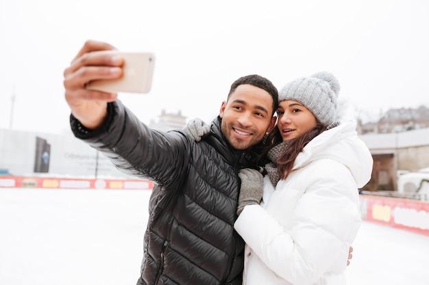Glückliches liebendes paar, das an eisbahn im freien skatet. mach ein selfie.