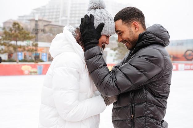Glückliches liebendes paar, das an eisbahn im freien skatet.