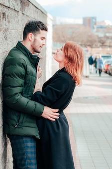 Glückliches liebendes paar, das auf der straße lächelt und umarmt. zwei glückliche menschen liebesgeschichte - medium long shot portrait